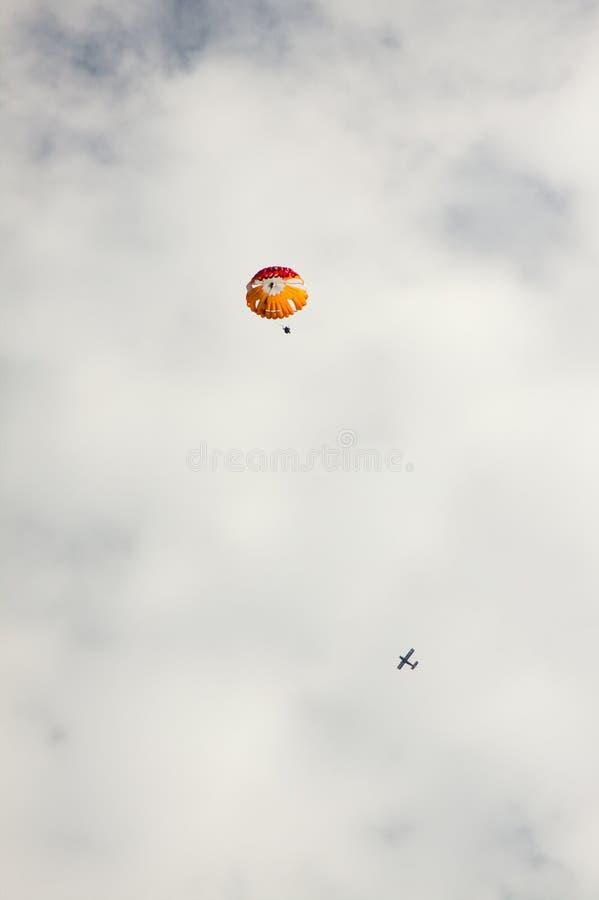 Воздушные судн и парашют на предпосылке облаков стоковые изображения rf