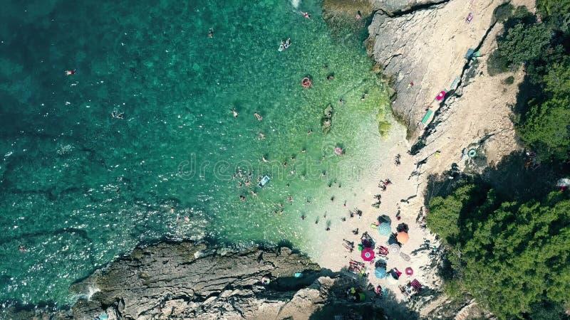 Воздушный верхней части взгляд вниз малого толпить скалистого пляжа на Адриатическом море Время летних каникулов стоковые изображения