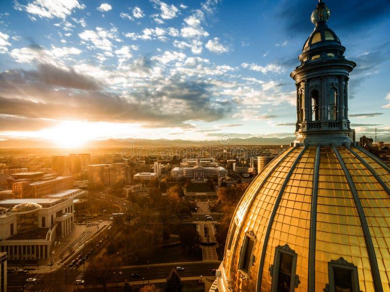 Воздушный фотоснимок трутня - сногсшибательный золотой заход солнца над зданием столицы государства Колорадо & скалистыми горами, стоковые фото