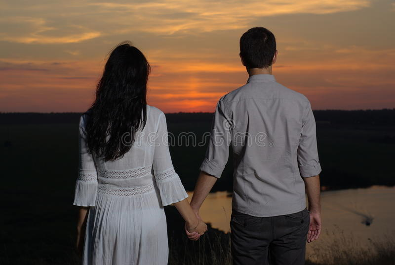 Возлюбленн пар на заходе солнца и озере стоковая фотография