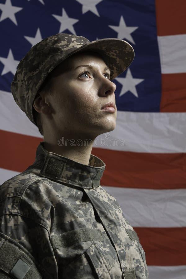 Воинская женщина перед флагом США, вертикальная воинская женщина перед флагом США, вертикальным стоковое изображение