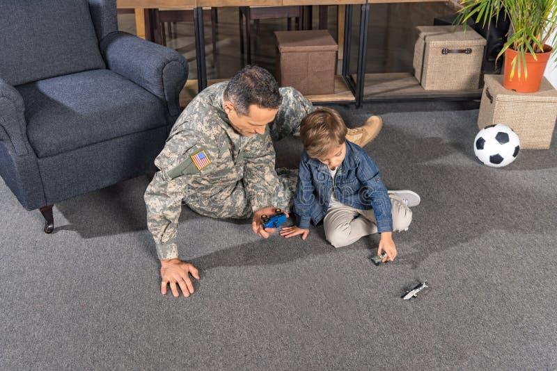 воинский отец и сын играя с игрушками пока сидящ на поле стоковые изображения