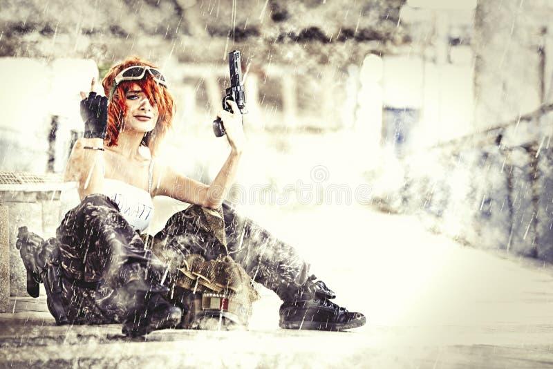 Воинский солдат женщины с оружием на войне Сидеть с дождем стоковые фото