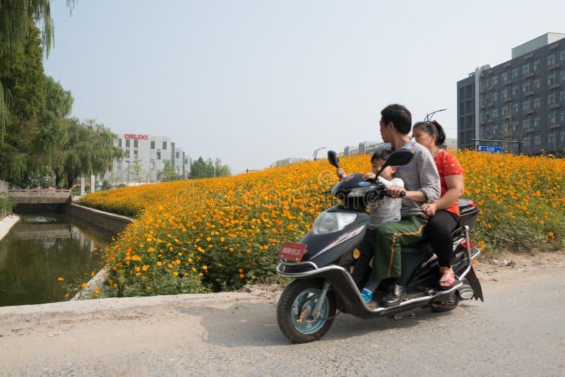 Вокруг Китая - семьи на электрическом мотоцикле стоковая фотография rf