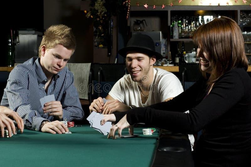 вокруг людей играя таблицу покера стоковая фотография rf