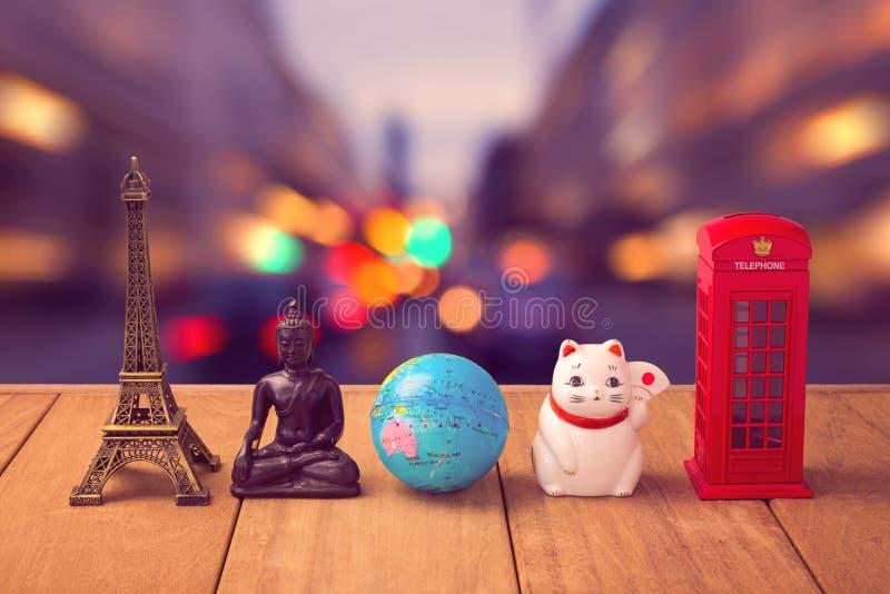 вокруг мира перемещения принципиальной схемы Сувениры со всего мира на деревянном столе над предпосылкой bokeh города стоковые фото