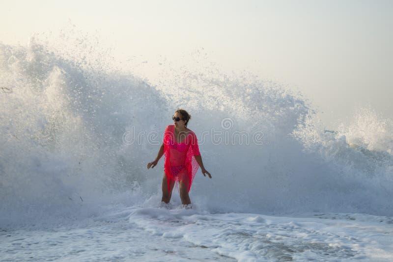 Волна 2 метров удивляет молодую женщину на seashore/ стоковые изображения rf
