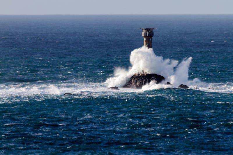 Волна разбивая над маяком Longships стоковое фото