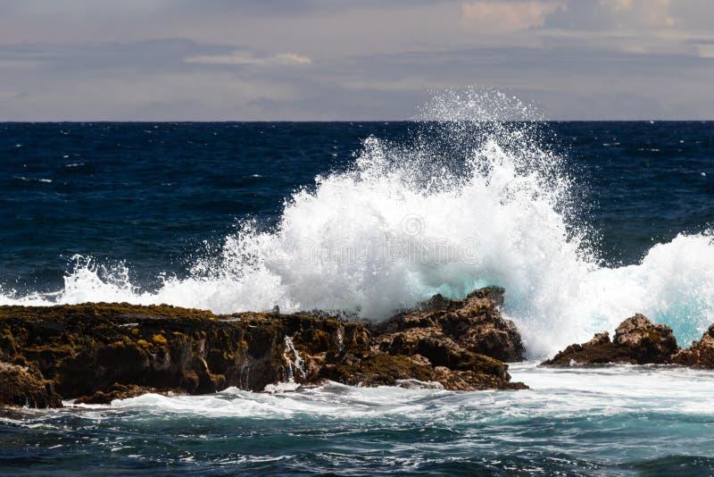 Волна разбивая на темном утесе лавы; белый брызг в воздухе, темном океане и облаках в предпосылке Пляж отработанной формовочной с стоковая фотография