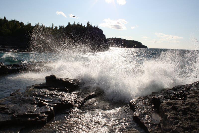 Волна ударила по скалистому берегу стоковые изображения