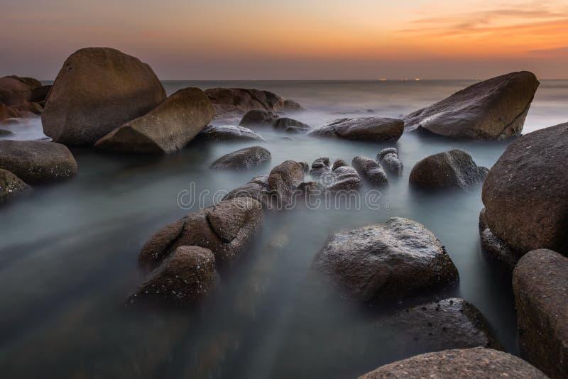Волна утеса и спокойного моря во времени захода солнца стоковые изображения rf