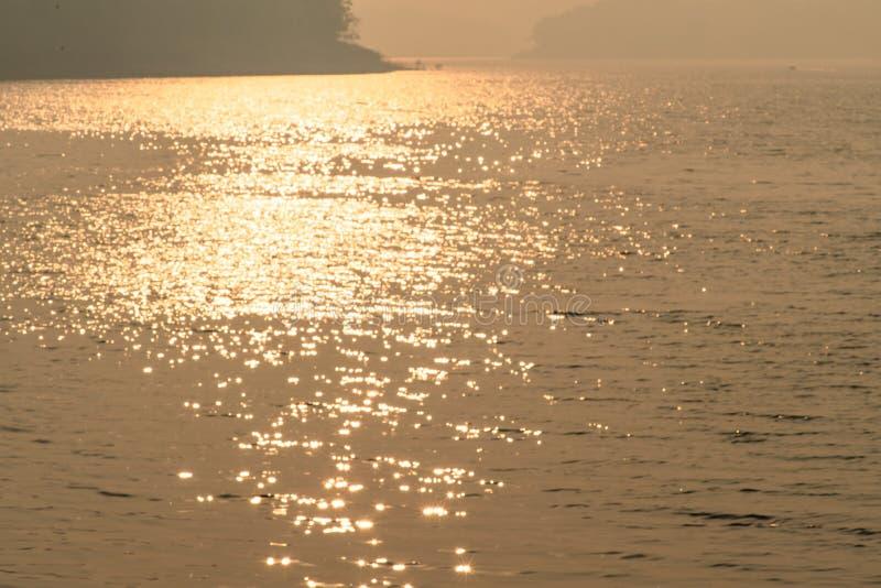 Волнистая поверхность воды с блестящим оранжевым светом солнца и черными горами на заднем плане стоковые фото