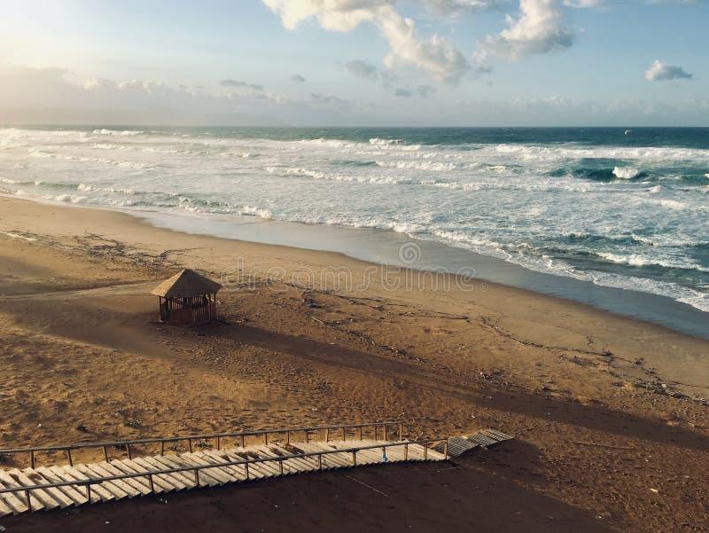 Волнистое Средиземное море с лестницами и хижина на времени захода солнца в Skikda Алжире стоковые фотографии rf