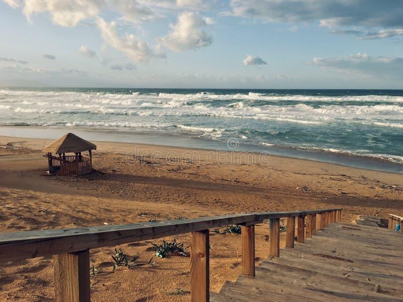 Волнистое Средиземное море с лестницами на времени захода солнца в Skikda Алжире стоковые изображения