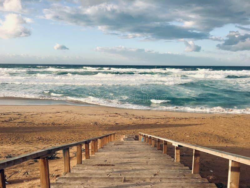 Волнистое Средиземное море с лестницами на времени захода солнца в Skikda Алжире стоковое изображение rf