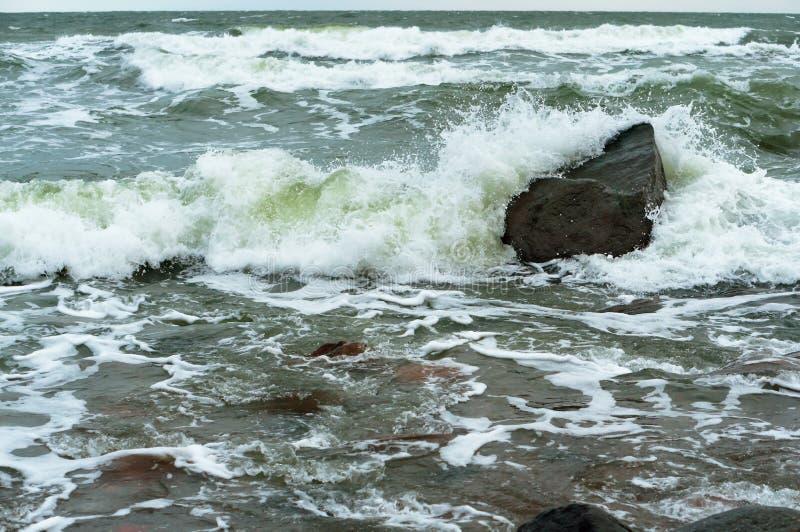 Волны брызгают на береге, волны побили против утесов стоковое фото