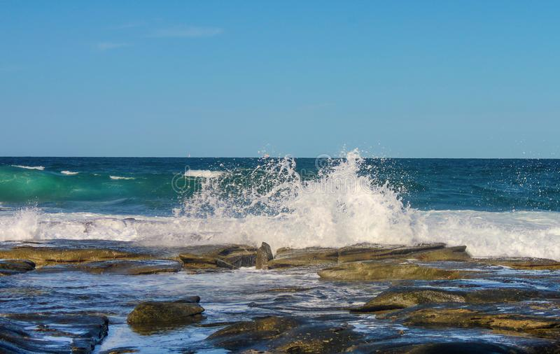 Волны брызгая против утесов как другой крен внутри с кораблями на горизонте океана стоковое изображение