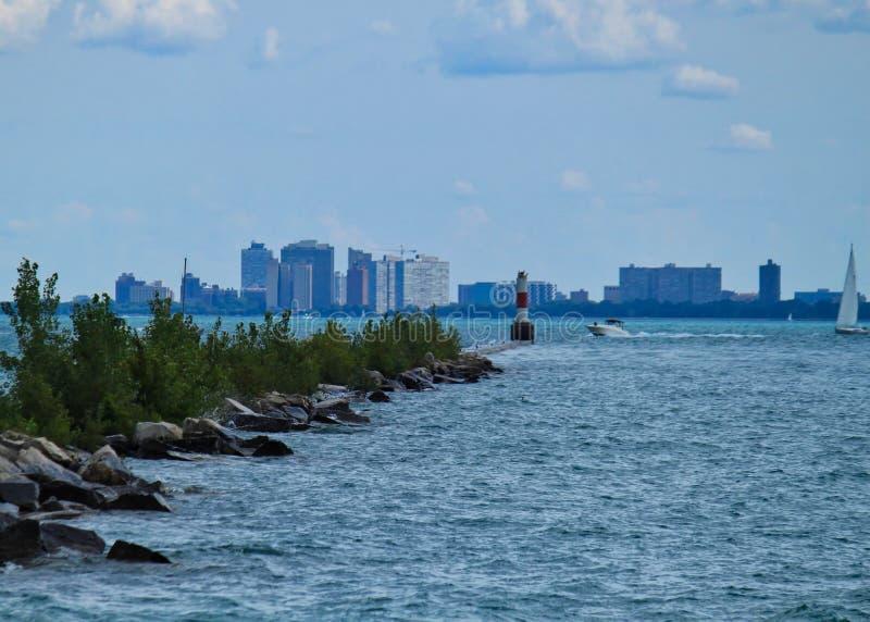 Волны вод Lake Michigan разбивают против ломать стену по мере того как шлюпки путешествуют мимо с горизонтом Чикаго позади стоковое фото