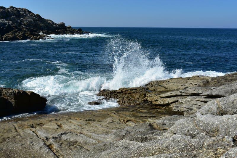 Волны ломая против утесов Дикие море, скала и открытое море Белая пена, голубое небо, солнечный день Галиция, Испания стоковые изображения