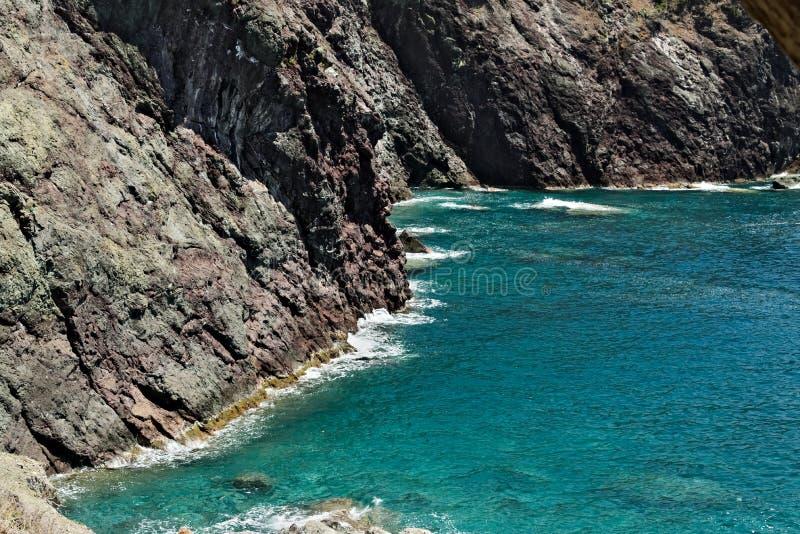 Волны моря ломают на утесах Ligurian горы Около Cinque Terre seascape с голубым морем и темный - красные утесы E стоковая фотография rf