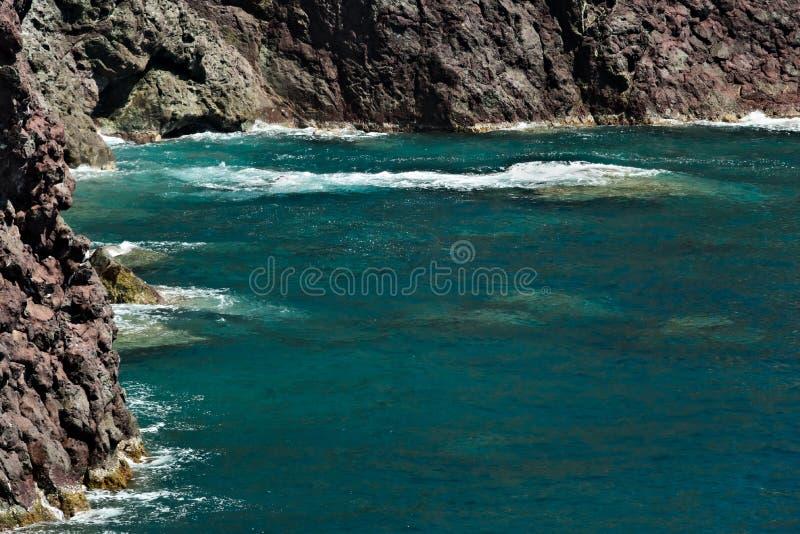 Волны моря ломают на утесах Ligurian горы Около Cinque Terre seascape с голубым морем и темный - красные утесы E стоковое фото