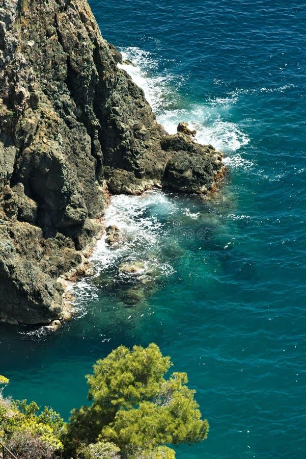 Волны моря ломают на утесах Ligurian горы Около Cinque Terre seascape с голубым морем и темный - красные утесы E стоковое фото rf
