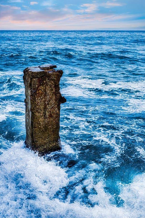 Волны моря ударяя старый конкретный штендер стоковая фотография rf