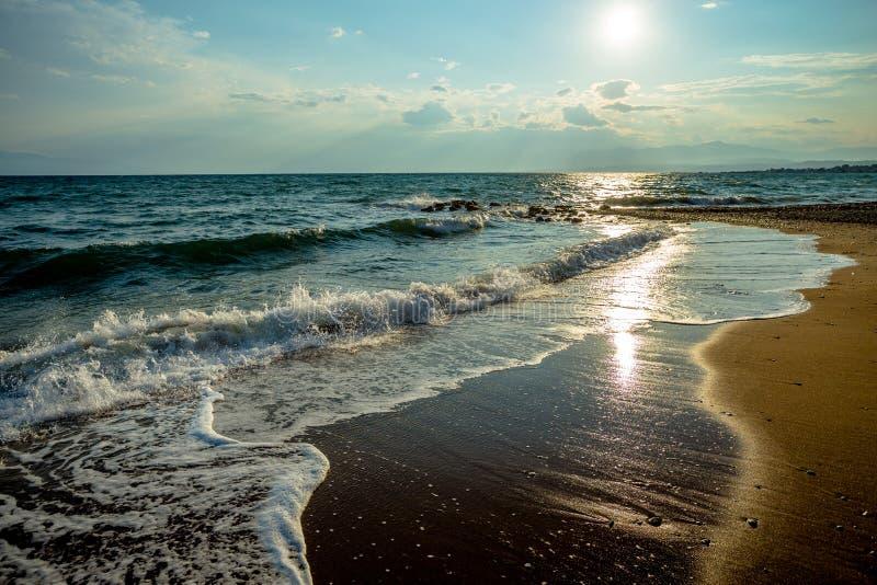 Волны на греческом песчаном пляже на яркий солнечный день во время праздников стоковая фотография rf