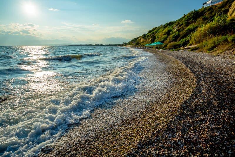 Волны на греческом Pebble Beach на яркий солнечный день во время праздников стоковые фотографии rf