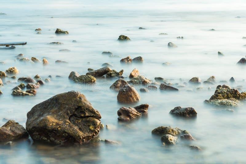 Волны на каменных водах пляжа окаймляют абстрактную предпосылку моря r стоковые фотографии rf