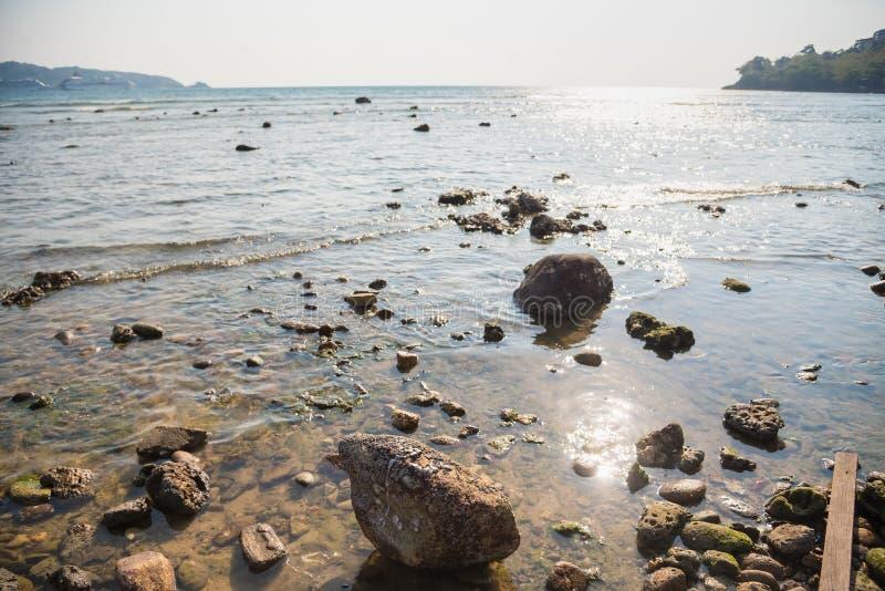Волны на каменных водах пляжа окаймляют абстрактную предпосылку моря r стоковое фото