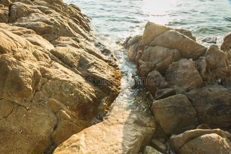 Волны на каменных водах пляжа окаймляют абстрактную предпосылку моря r стоковое изображение