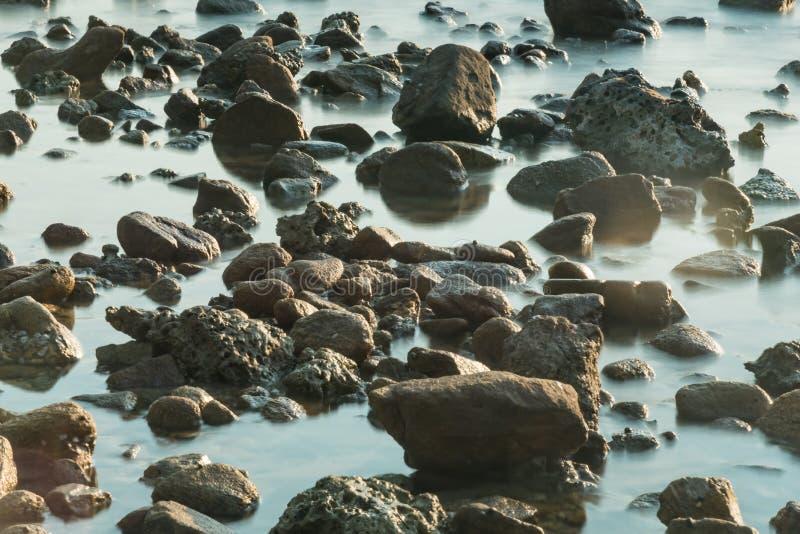 Волны на каменных водах пляжа окаймляют абстрактную предпосылку моря r стоковая фотография