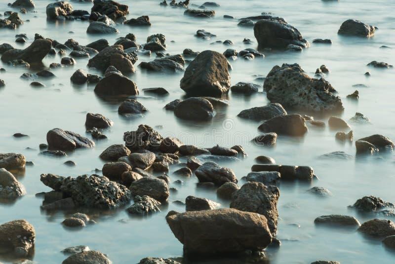 Волны на каменных водах пляжа окаймляют абстрактную предпосылку моря r стоковое фото rf