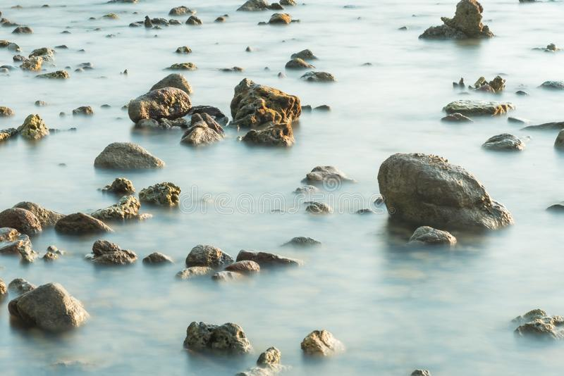 Волны на каменных водах пляжа окаймляют абстрактную предпосылку моря r стоковое изображение rf