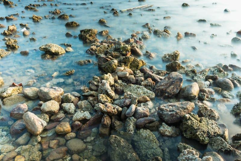 Волны на каменных водах пляжа окаймляют абстрактную предпосылку моря r стоковые изображения