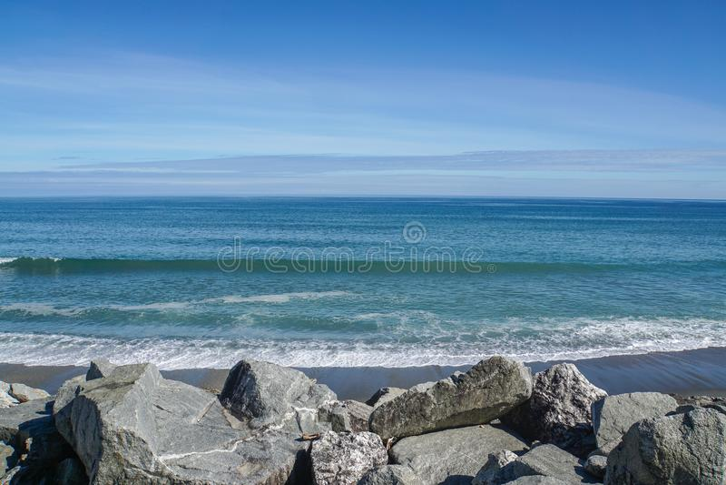 Волны от голубого моря на береге с большим передним планом утеса стоковые изображения rf