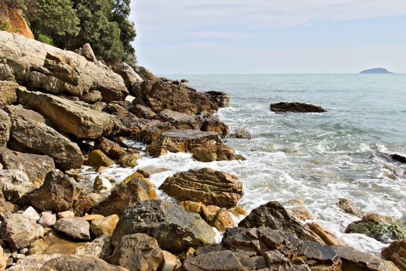 Волны перерыва моря на утесах Утесы горы желтого цвета стоковые изображения