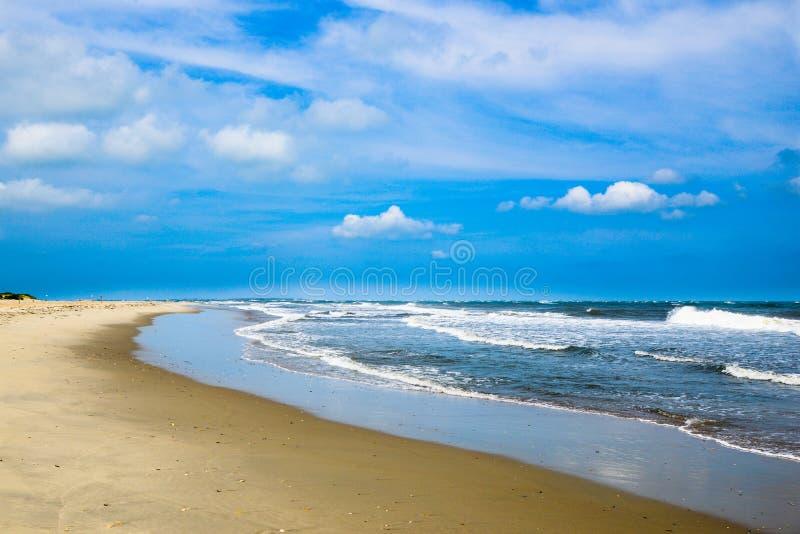 волны пляжа разбивая синь заволакивает небо стоковое фото rf