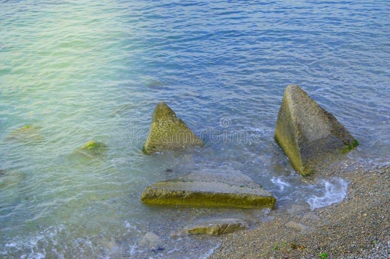 Волны подпаливания моря на огромных валунах на береге стоковая фотография rf