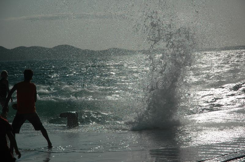 Волны против людей на солнечный день стоковое фото rf