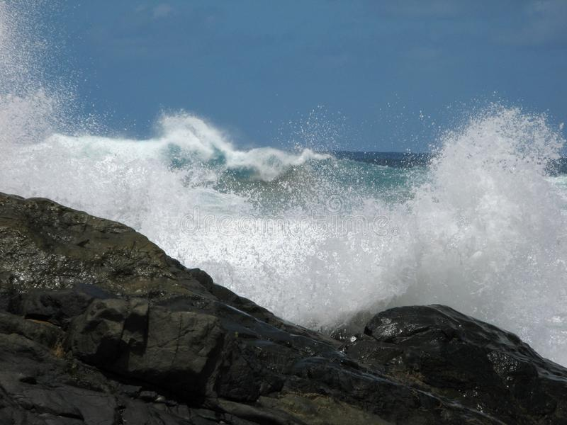 Волны разбивая на черном, вулканическом береге стоковое изображение