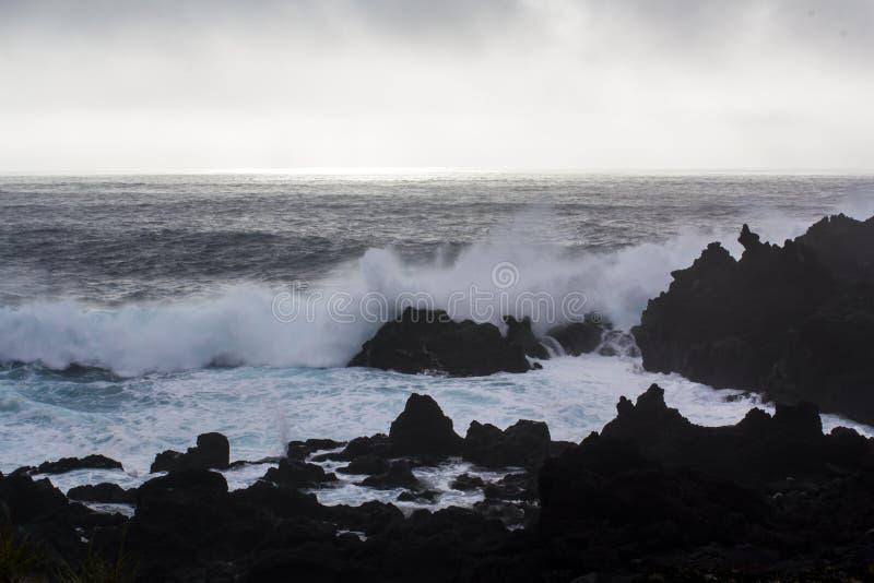 Волны разбивая против черных образований вулканической породы стоковое изображение