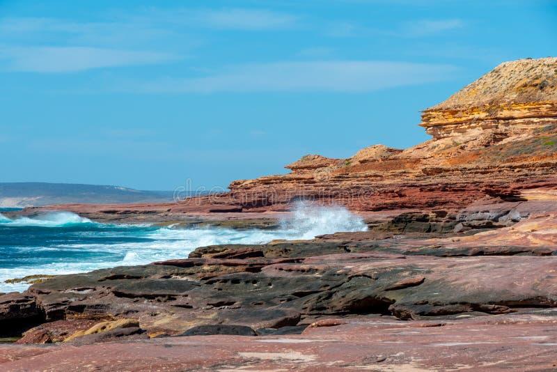 Волны ударяя побережье утеса с другими цветами от красного цвета для того чтобы пожелтеть в национальном парке Австралии Kalbarri стоковые изображения rf
