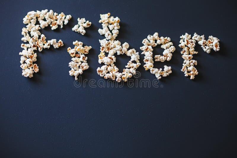 ` Волокна ` слова сделанное из свежего попкорна на темном штейне покрасило поверхность стоковые фото