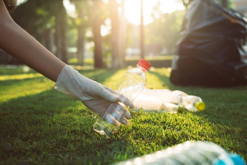 Волонтерская женщина держит пластиковую бутылку на зеленой траве, хороший сознательный ум, избавление от рециркуляции и утилизаци стоковые фотографии rf