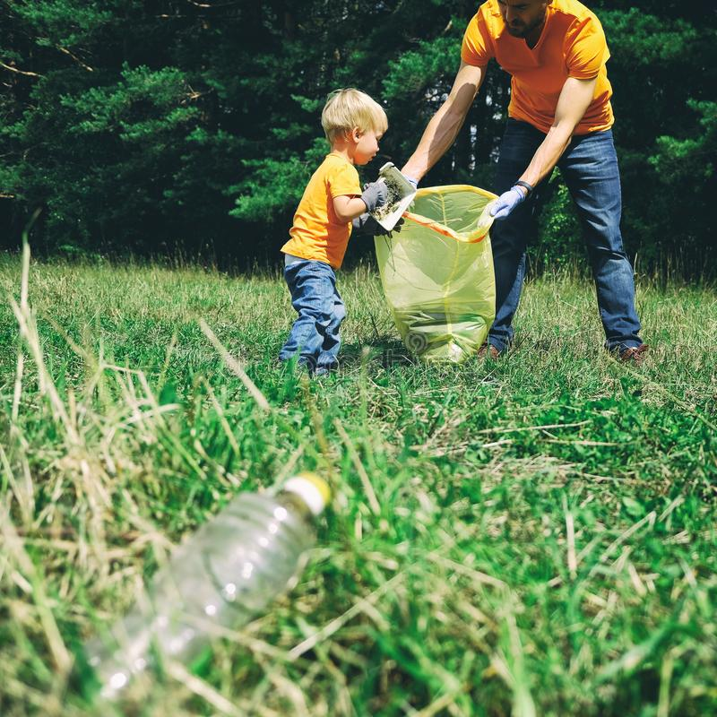 Волонтеры комплектуя вверх сор в парке Отец и его сын малыша очищая вверх мальчика леса собирают пластиковый отброс дальше стоковая фотография