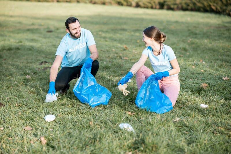Волонтеры очищая общественный парк от хлама стоковое фото rf