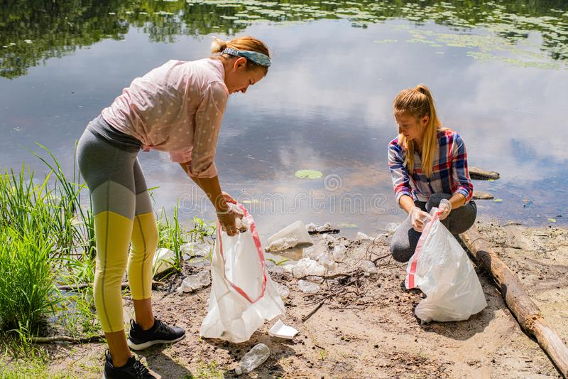 Волонтеры очищая отброс около реки Женщины комплектуя вверх пластмассу бутылки в озере, загрязнении и окружающей среде стоковые изображения rf