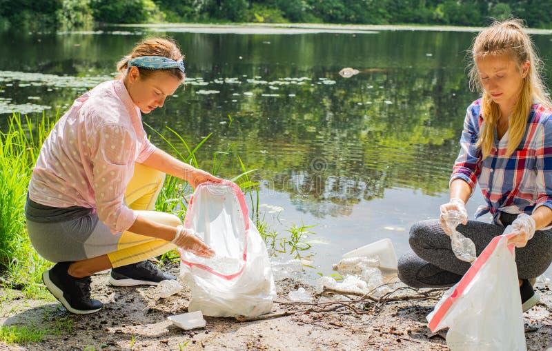Волонтеры очищая отброс около реки Женщины комплектуя вверх пластмассу бутылки в озере, загрязнении и окружающей среде стоковые фото